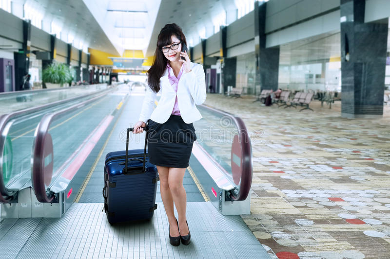 Businesswoman making a phone call at airport stock photography