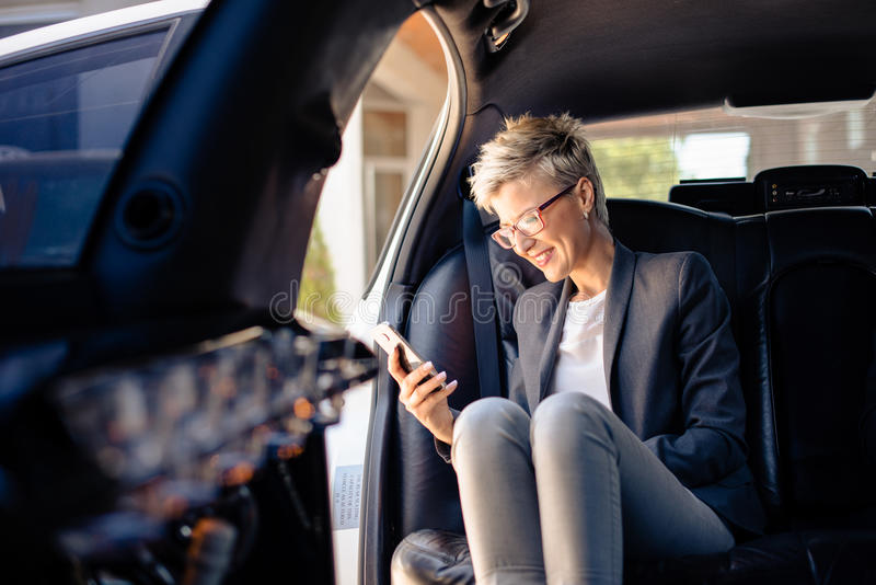 Businesswoman making phone call in limousine royalty free stock photos