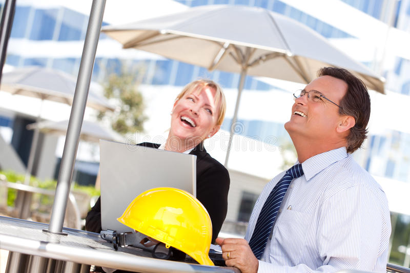 Businesswoman and Man Laughing While Working stock photos