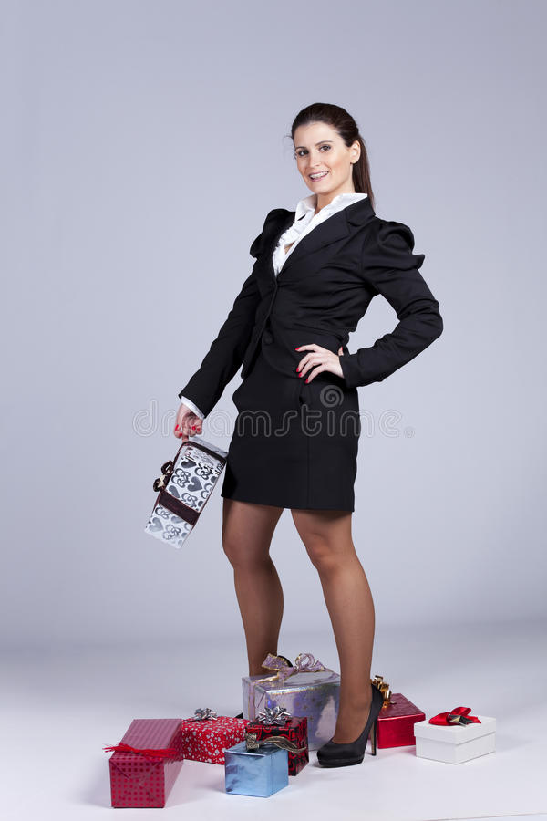 Businesswoman with many gift packages. Businesswoman with a lot of gift packages (isolated on gray royalty free stock photo