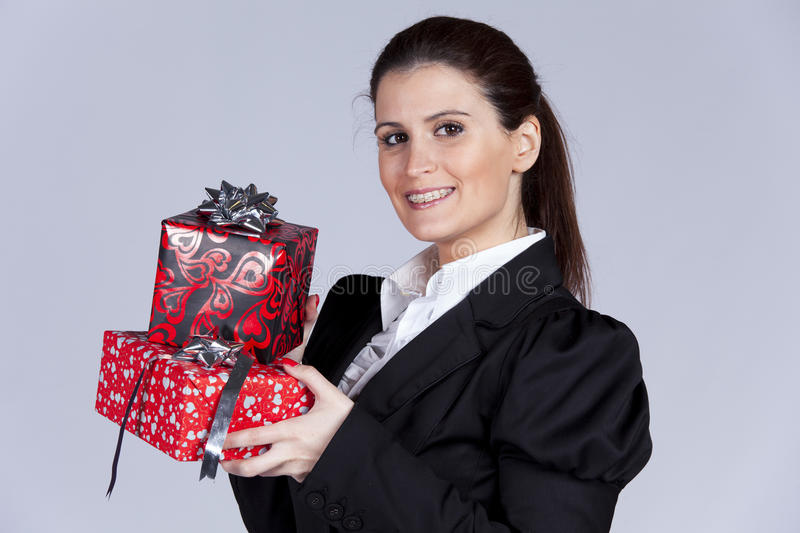 Businesswoman with many gift packages. Businesswoman with a lot of gift packages ( on gray stock images