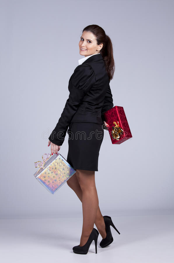 Businesswoman with many gift packages. Businesswoman with a lot of gift packages ( on gray royalty free stock images