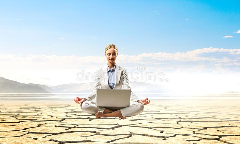 Businesswoman meditating in front of laptop royalty free stock photos