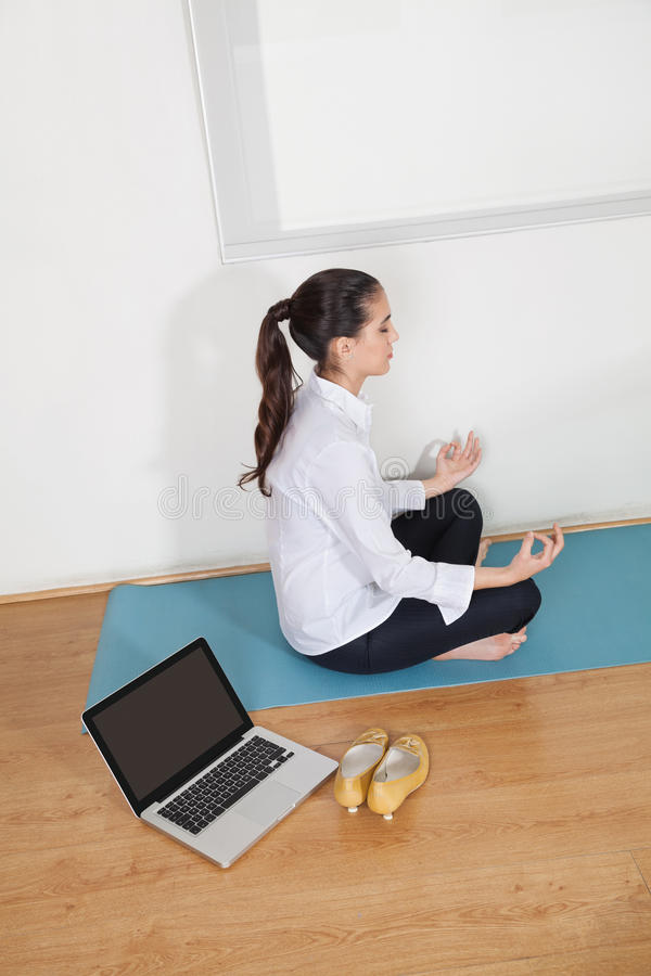 Businesswoman meditating in office stock image