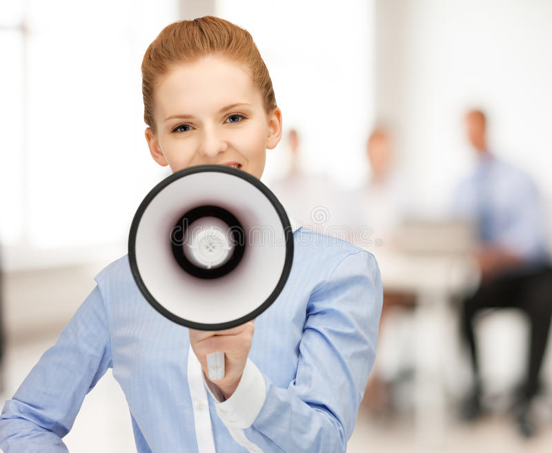 Businesswoman with megaphone in office. Close up of friendly businesswoman with megaphone in office royalty free stock images