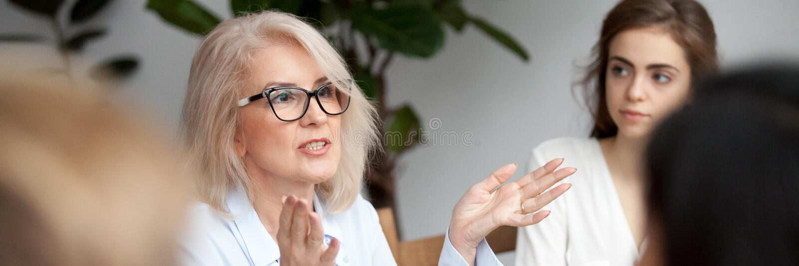 Businesswoman mentor give instructions to young professional intern during seminar. Aged businesswoman coach teach give instructions knowledge to new employees royalty free stock image