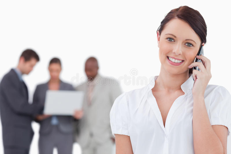 Businesswoman with mobile phone and co-workers royalty free stock image