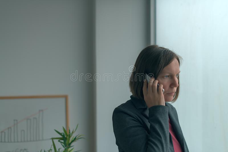 Businesswoman in mobile phone conversation by the office window royalty free stock photos