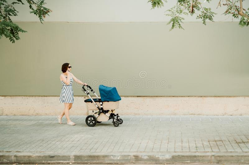 Businesswoman mother and your baby in cart walking on urban sidewalk - stock photo stock photos