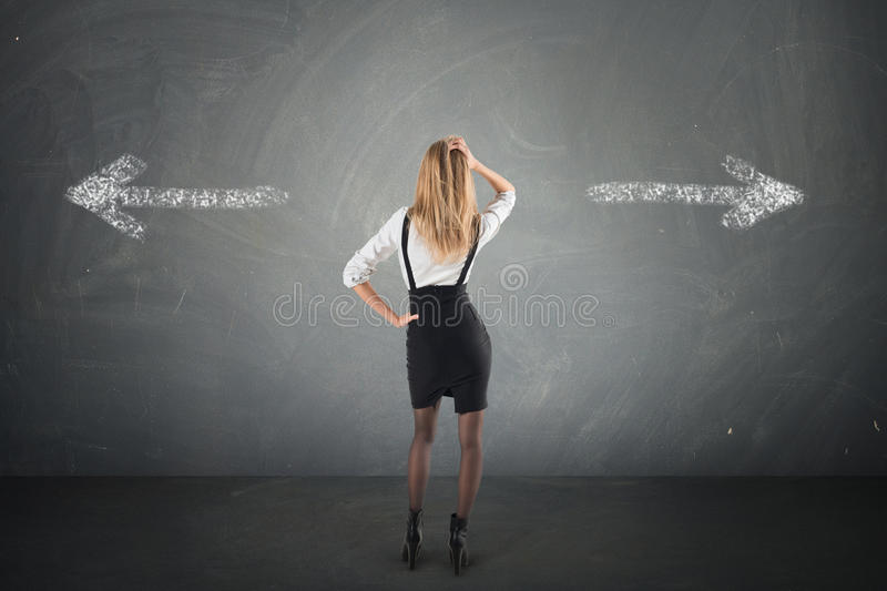 Businesswoman must choose between different destinations looking at two arrows showing two different directions. Businesswoman must choose between different royalty free stock images