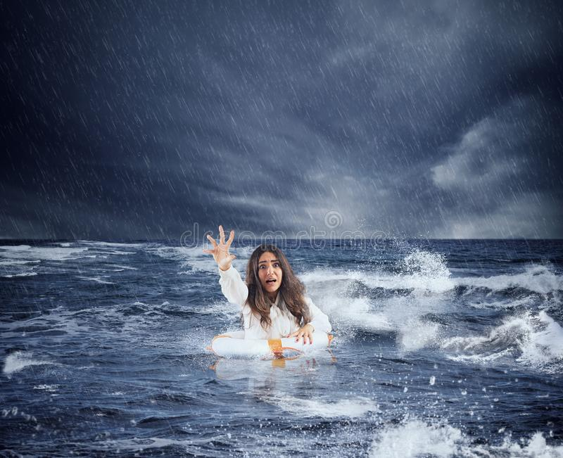 Businesswoman in the ocean with lifebelt asks help during a storm royalty free stock photography