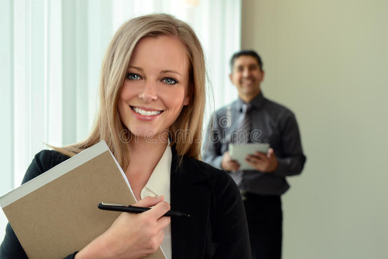 Businesswoman In Office. Beautiful businesswoman holding pen and pad with coworker in background royalty free stock image