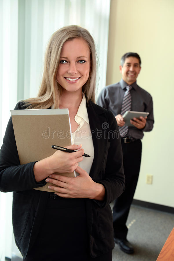 Businesswoman In Office. Beautiful businesswoman holding notepad with coworker in background royalty free stock image