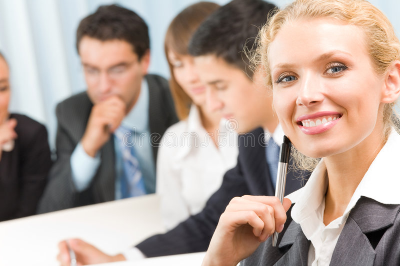Businesswoman at office. Businesswoman and business-team at office meeting royalty free stock images