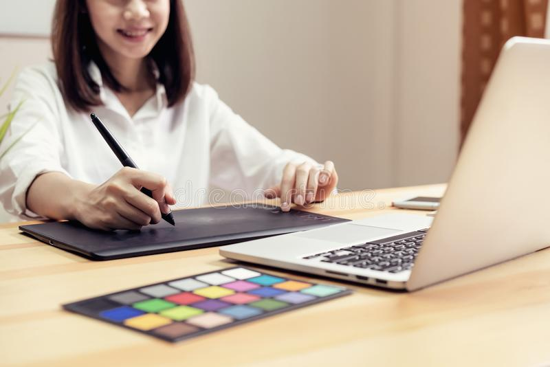 Businesswoman in office in casual shirt. Use computer for graphic designer. stock image