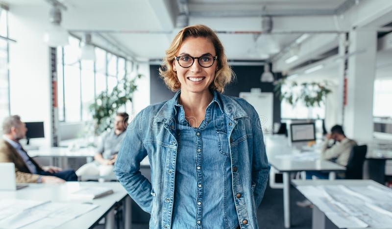 Businesswoman in office with colleagues in background. Businesswoman standing in foreground with male colleagues in background. Attractive young female looking royalty free stock photos