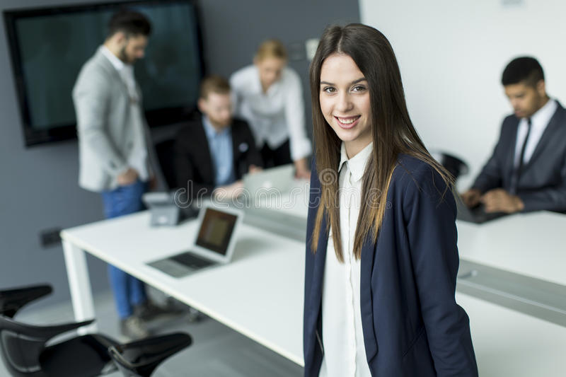 Businesswoman. In the office with her colleagues behind royalty free stock photos
