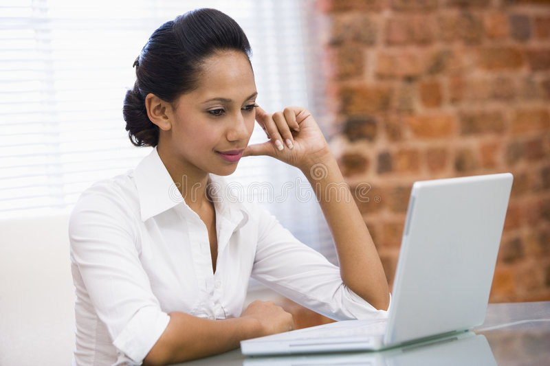 Businesswoman in office with laptop royalty free stock images