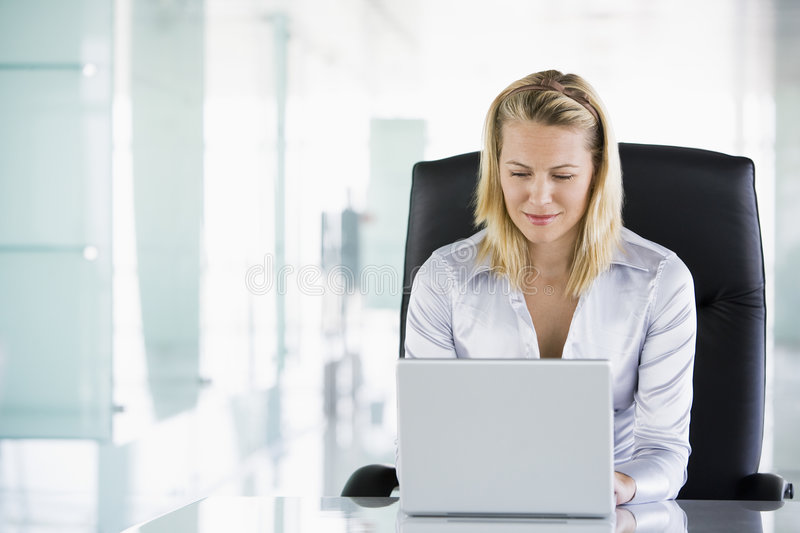 Businesswoman in office using laptop