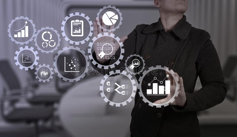 Businesswoman with an open hand as showing something. Business data analytics management with connected gear cogs with KPI financial charts and graph stock image