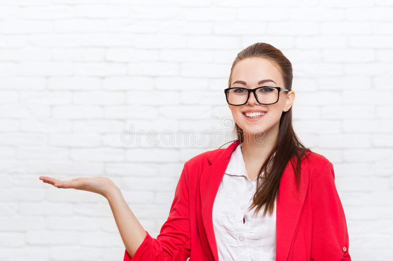Businesswoman open palm hand gesture to copy space wear red jacket glasses smile. Business woman over office wall royalty free stock photography