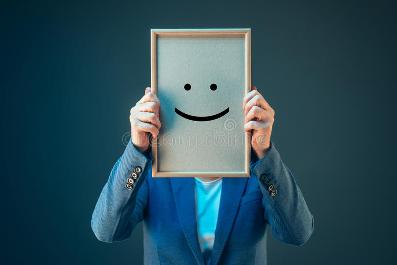 Businesswoman is optimistic, holding smiley emoticon over face. Businesswoman is optimistic about her future in corporate business, holding printed happy smiley royalty free stock image