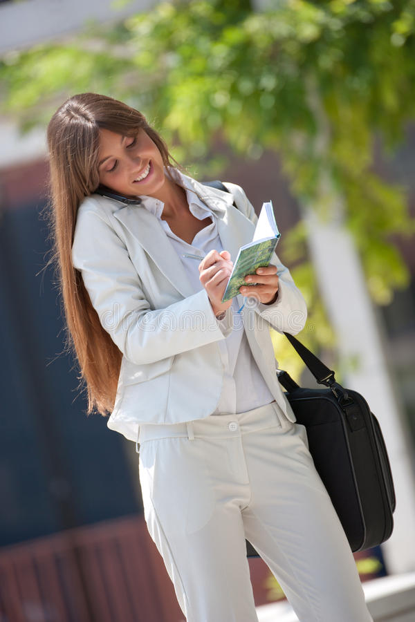 Businesswoman outdoors. Young businesswoman outdoors making a phone call while taking note royalty free stock photography