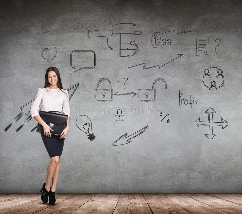 Businesswoman over wall with icons background. royalty free stock images