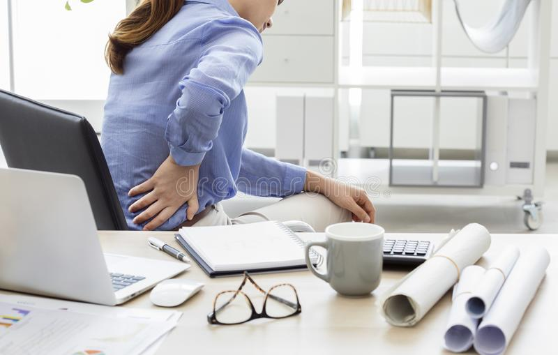 Businesswoman with pain in back stock photography