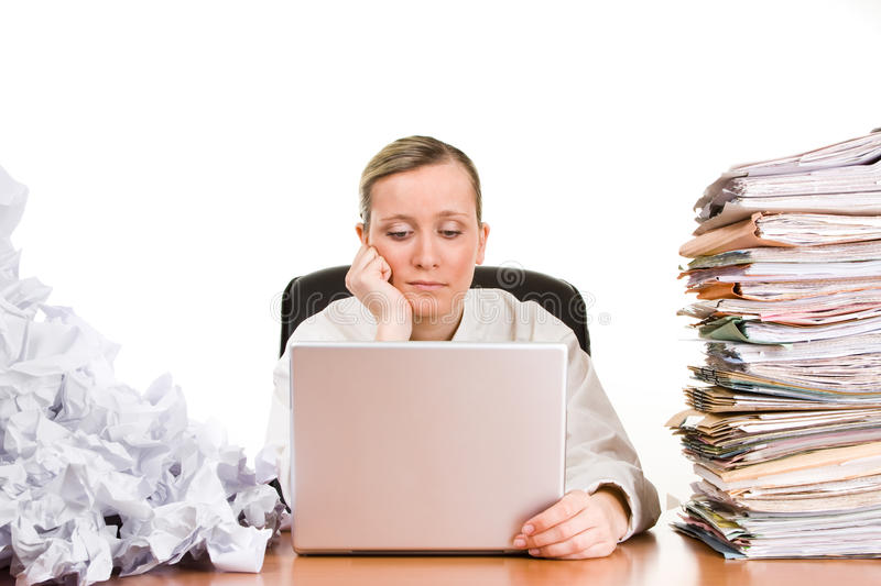 Businesswoman with paperwork. Thinking or tired businesswoman with stack of paperwork, pile of crumpled papers and a laptop computer royalty free stock image