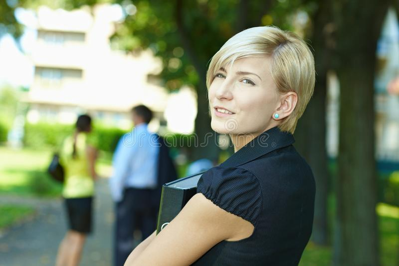 Businesswoman in park. Portrait of young businesswoman standing in sunny park, smiling royalty free stock photo