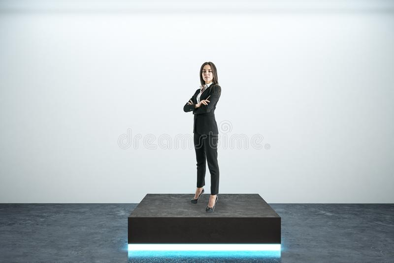 Businesswoman on pedestal. Businesswoman standing on illuminated pedestal in interior. Leadership and success concept royalty free stock images
