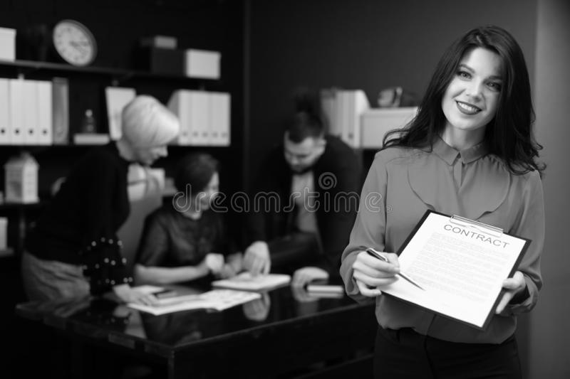 Businesswoman with pen and contract on background of Office workers discuss the project royalty free stock photography
