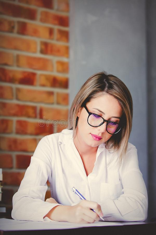 Businesswoman with pen on working place. Young businesswoman in glasses sitting on working place with pen. Brick wall on background stock photography