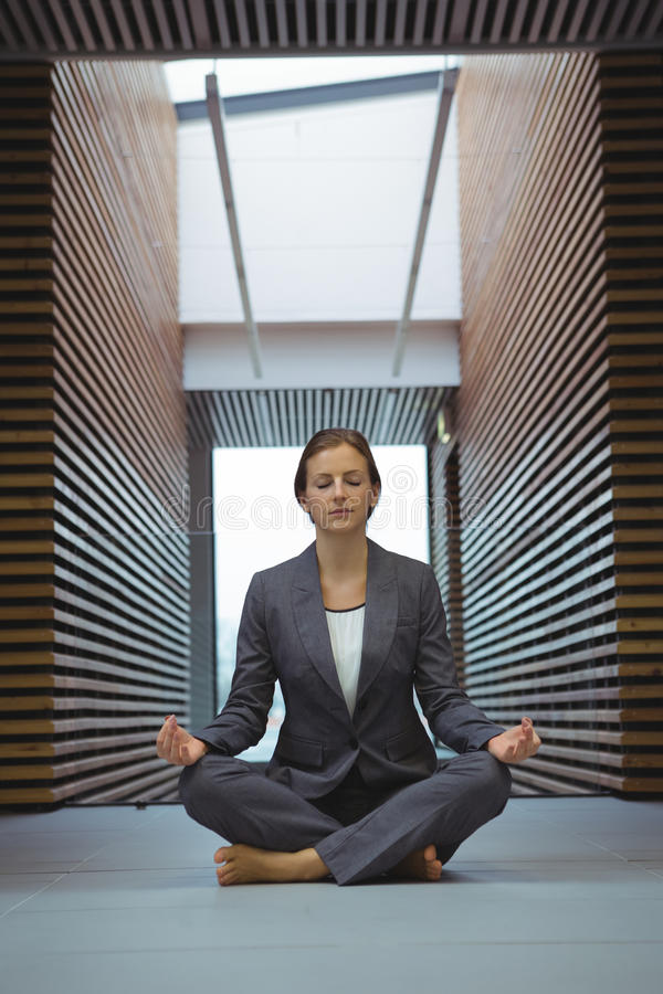 Businesswoman performing yoga in the corridor stock photo