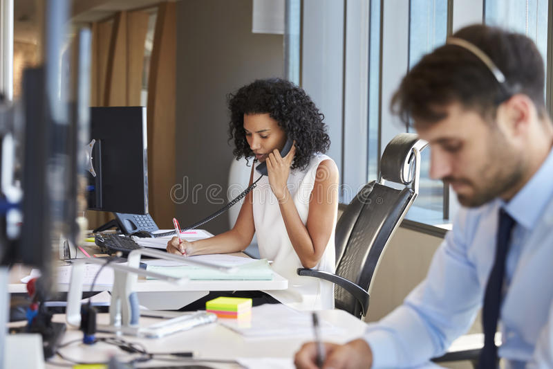 Businesswoman On Phone At Desk In Busy Office stock photo