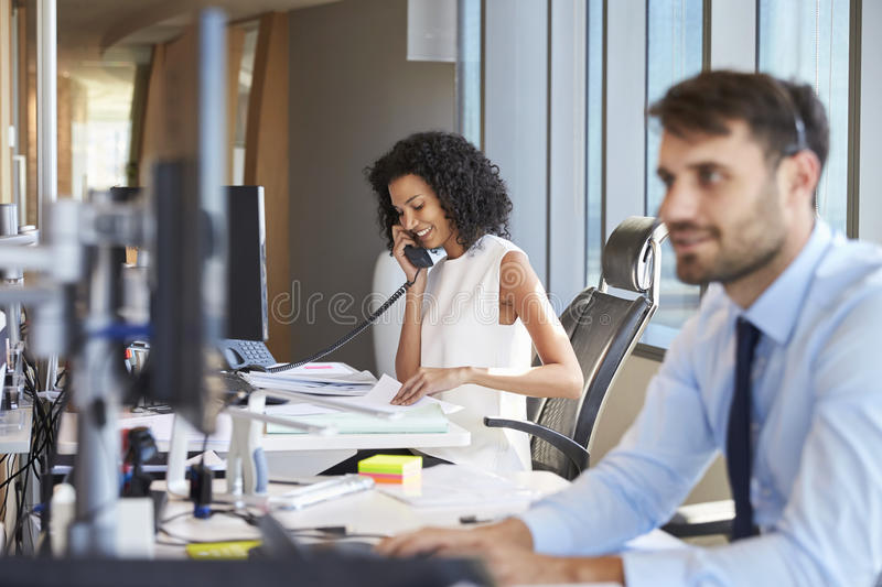 Businesswoman On Phone At Desk In Busy Office royalty free stock photography