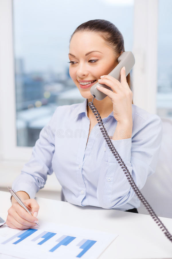 Businesswoman with phone, laptop and files. Business, technology and communication concept - smiling businesswoman with phone, laptop and files in office royalty free stock images