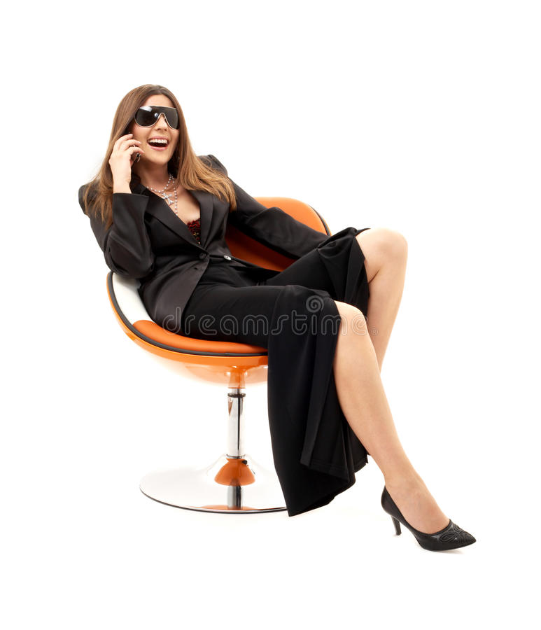 Businesswoman with phone in orange chair #2. Businesswoman with phone in orange chair over white royalty free stock images