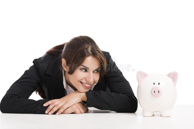 Businesswoman with a piggy bank. Beautiful hispanic business woman holding a piggy bank, isolated over white background royalty free stock photography