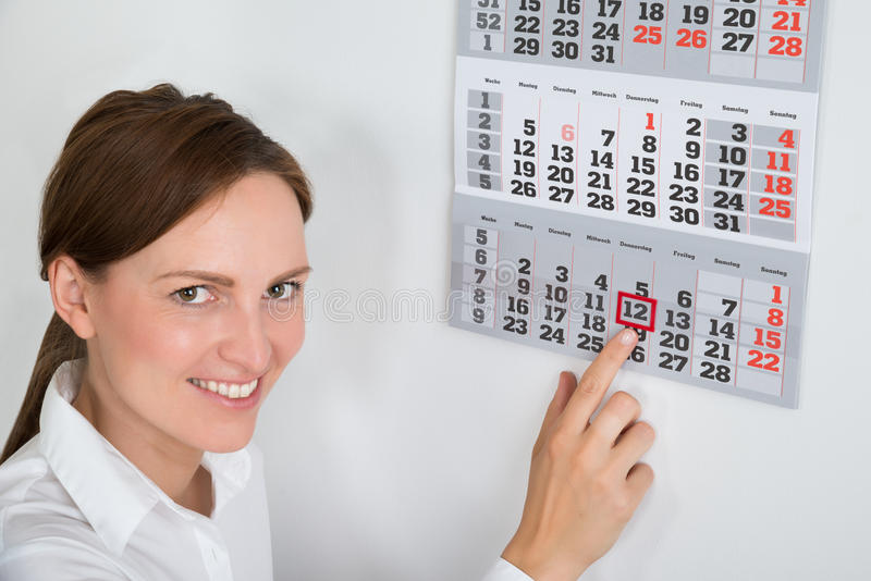 Businesswoman Placing Red Mark On Calendar Date. Close-up Of Young Businesswoman Placing Red Mark On Calendar Date royalty free stock image