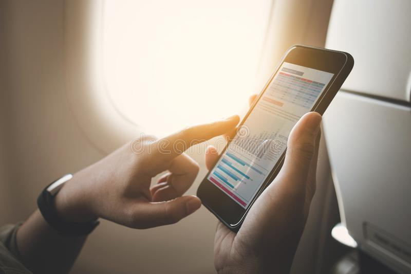 Businesswoman on plane using smartphone with graph on screen.Business technology royalty free stock photo