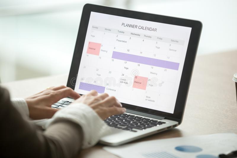 Businesswoman planning day using digital calendar on laptop, clo stock image