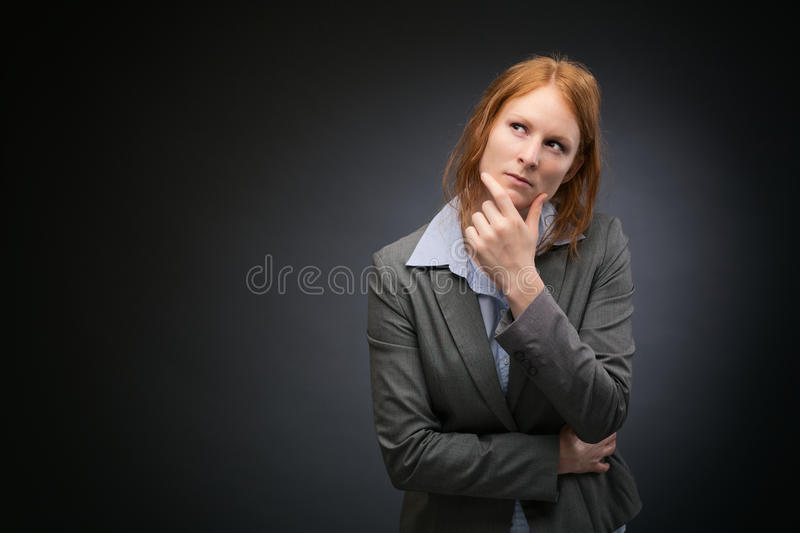Businesswoman with Plans or Vision. Studio portrait of a young businesswoman thinking or planning before a dark background with copy space stock photography