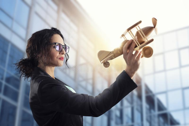 Businesswoman play with a toy aircraft. Concept of company startup and business success stock photo