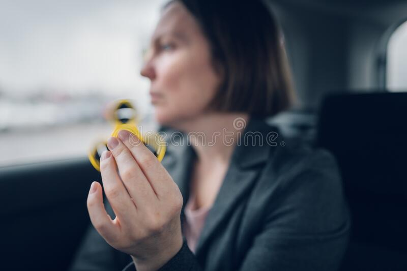 Businesswoman playing with fidget spinner in car. While sitting at the backseat of the vehicle and commuting to work, selective focus stock photos