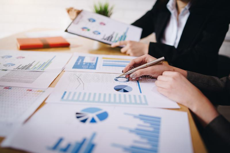 Businesswoman pointing pen on business document at meeting room. Discussion and analysis data charts and graphs showing the royalty free stock image