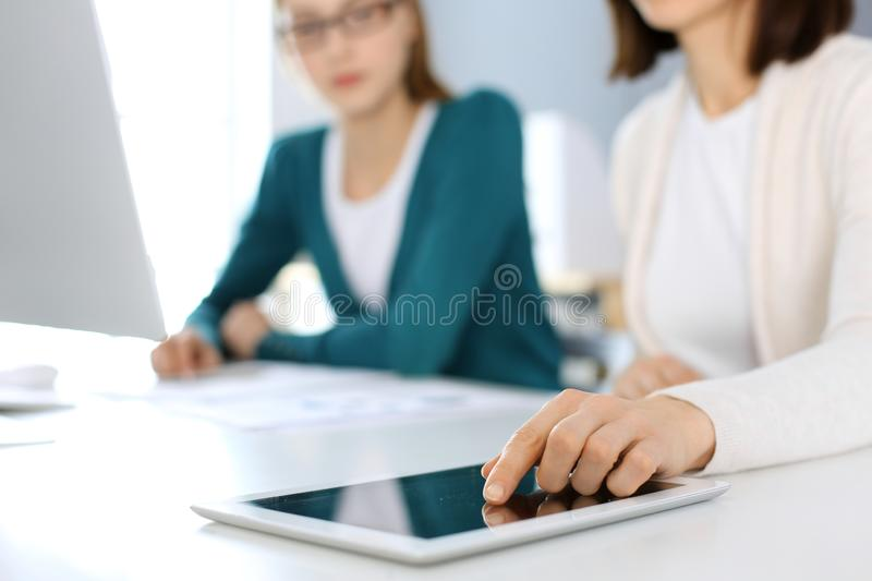 Businesswoman pointing at tablet computer screen while giving presentation to her female colleague. Group of business stock image