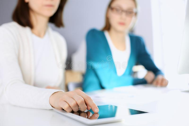 Businesswoman pointing at tablet computer screen while giving presentation to her female colleague. Group of business stock photography
