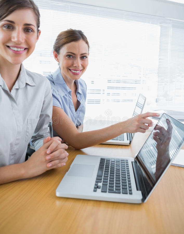 Businesswoman Pointing To Something On Laptop For Colleague Port Royalty Free Stock Photos